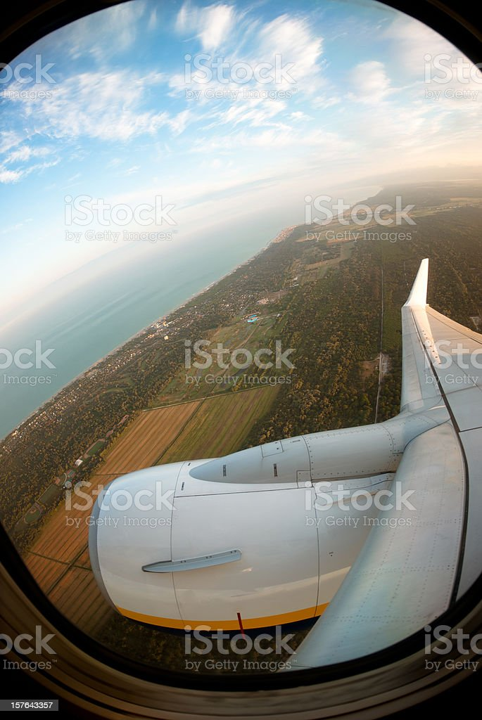 view from airplane porthole of the coastline on sunset royalty-free stock photo