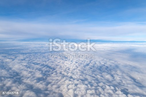 istock View from airplane window above the clouds with blue sky and cloudscape in sunlight morining. white wispy cirrus and cirrostratus clouds 874943718