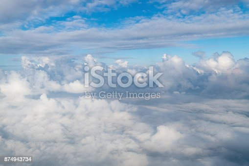istock View from airplane window above the clouds with blue sky and cloudscape in sunlight morining. white wispy cirrus and cirrostratus clouds 874943734