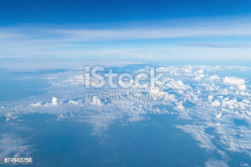 istock View from airplane window above the clouds with blue sky and cloudscape in sunlight morining. white wispy cirrus and cirrostratus clouds 874943756
