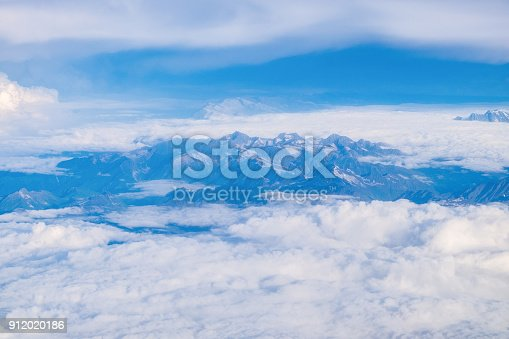 istock View from airplane window above the clouds with blue sky and cloudscape in sunlight morining. white wispy cirrus and cirrostratus clouds 912020186