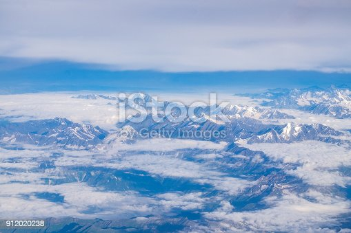 istock View from airplane window above the clouds with blue sky and cloudscape in sunlight morining. white wispy cirrus and cirrostratus clouds 912020238