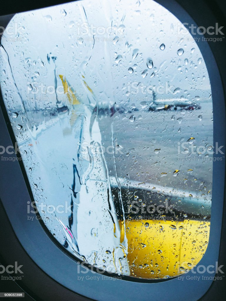 View From Airplane Window at Airport on a Rainy Day stock photo