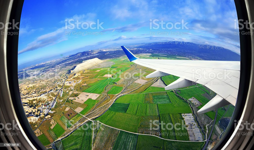 View from airplane window on fields and mountains stock photo
