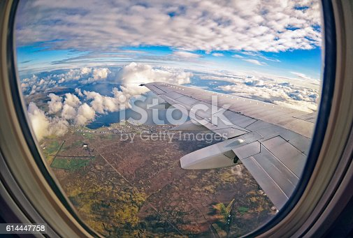 621114928istockphoto View from airplane window on green fields ,  clouds and sea 614447758