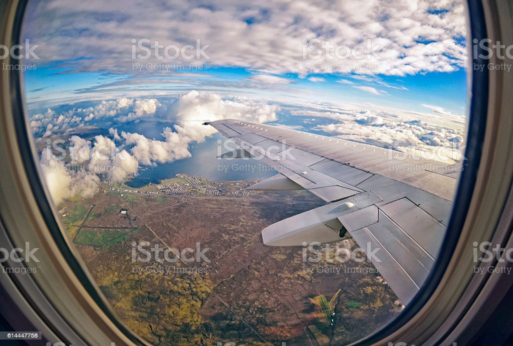 View from airplane window on green fields ,  clouds and sea stock photo