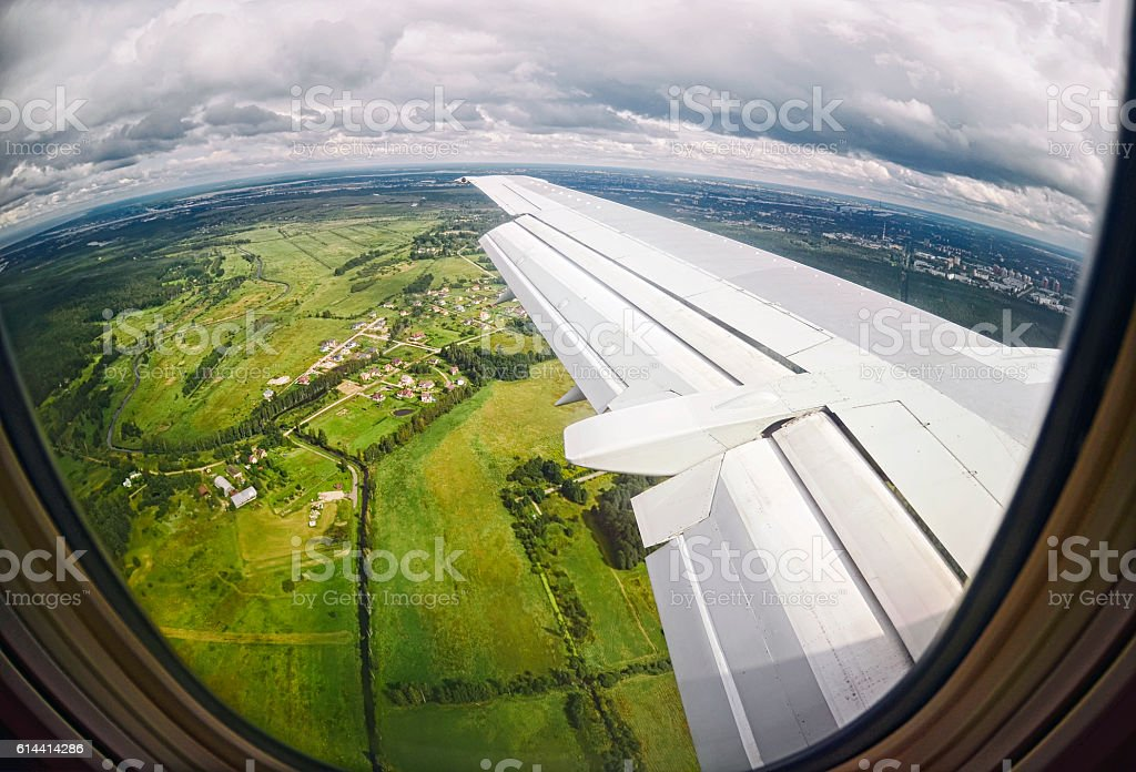 View from airplane window on green fields stock photo