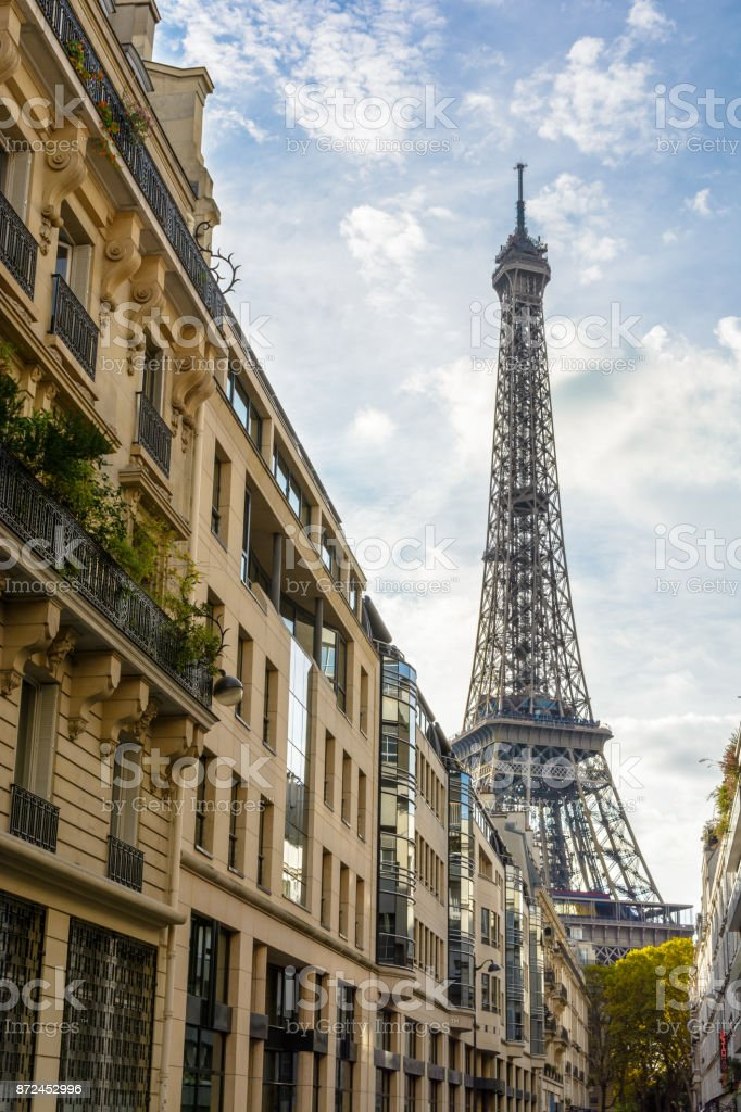 View from an adjacent street of the majestic Eiffel Tower in its immediate neighborhood with typical parisian buildings in the foreground stock photo