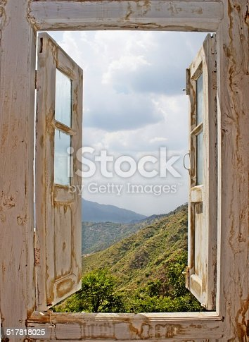 View of the mountains and clouded sky from an open old white wood window. Ideal for concepts related to outdoors, nature, exploration, peace, and inspiration.