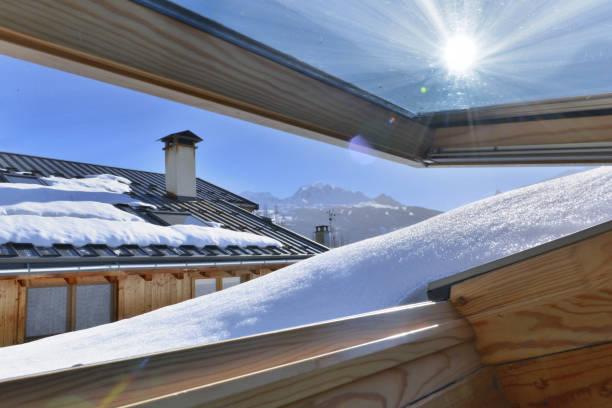 uitzicht vanaf een opening raam op een dakbedekking met sneeuw in een alpine Cottage foto