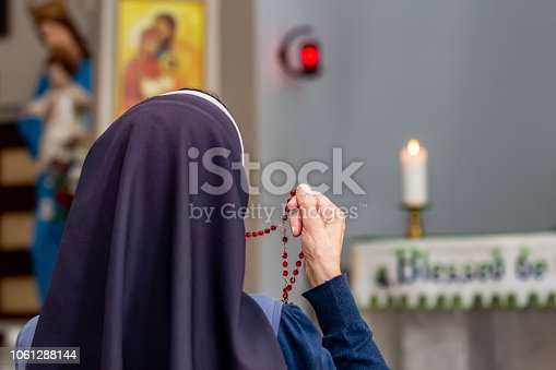 istock View from back of a religious sister holding rosary and praying. 1061288144