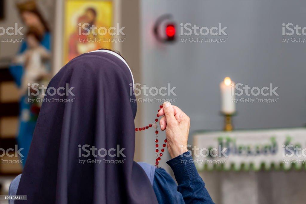 Vista de trás uma irmã religiosa segurando o Rosário e rezar. - foto de acervo
