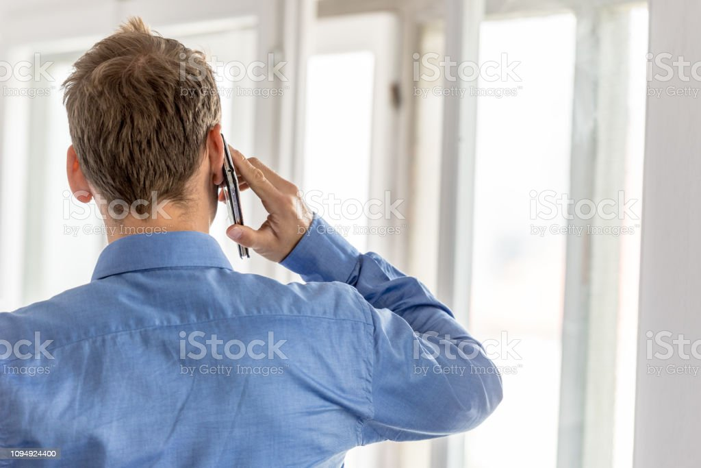 View from behind of a businessman talking on a mobile phone stock photo