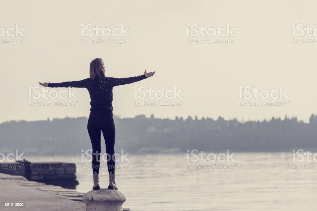 Blick von hinten auf eine junge Frau auf Zement Poller - Lizenzfrei Anlegestelle Stock-Foto
