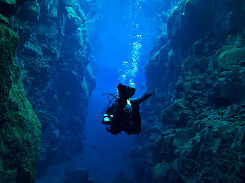 View From Behind Single Scuba Diver With Bubbles Above At Continental Split At Silfra In Deep Section At Pingvellir National Park Stock Photo - Download Image Now