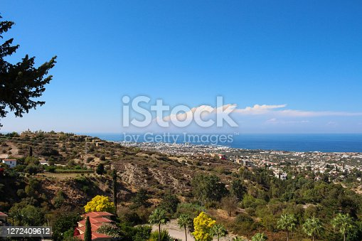 View from Bellapais Abbey of the restaurant's roofs, trees, Kyrenia, sea and blue sky. Cyprus.