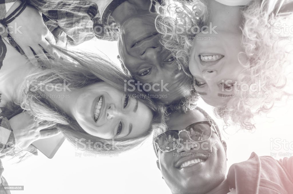 View from below. Group of young people making a circle. They lean towards the camera laughing stock photo