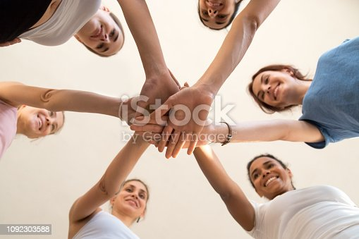 istock View from below happy diverse girls putting hand together 1092303588