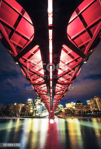 Calgary, Canada - Calgary's skyline at night, reflected in the Bow river below the red lattice pattern of the Peace Bridge. The bridge was designed by Santiago Calatrava, and opened in 2012.