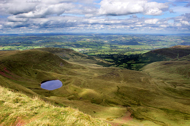 View from Corn Du in the Brecon Beacons A view looking towards a Tarn from Corn du, within the Brecon Beacons in South Wales. There is a large amount of clouds with a blue sky background. The scenery is mountainous and very undulating. brecon beacons stock pictures, royalty-free photos & images