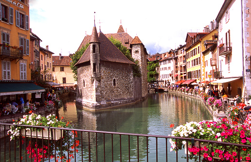 View from footbridge festooned with flowers along canal in downtown Annecy Haute-Savoie France Europe