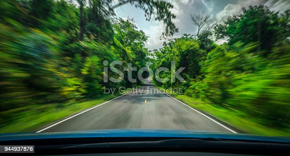 istock View from front of blue car on asphalt road and speed motion blur on highway in summer with green trees forest at countryside 944937876