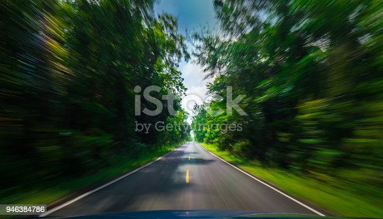 istock View from front of blue car on asphalt road and speed motion blur on highway in summer with green trees forest at countryside 946384786