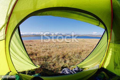 istock View from green light green tent to the shore of a mountain lake amid snow-capped peaks under the clouds and blue sky Plateau Ukok Altai mountains Siberia Russia 820575460