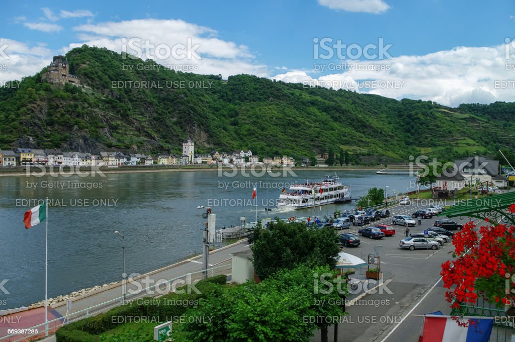 View from hotel window on Sankt-Goar embankment and Snak Goarshausen medieval village and Rhine vineyards on slope of the hills in Germany. stock photo