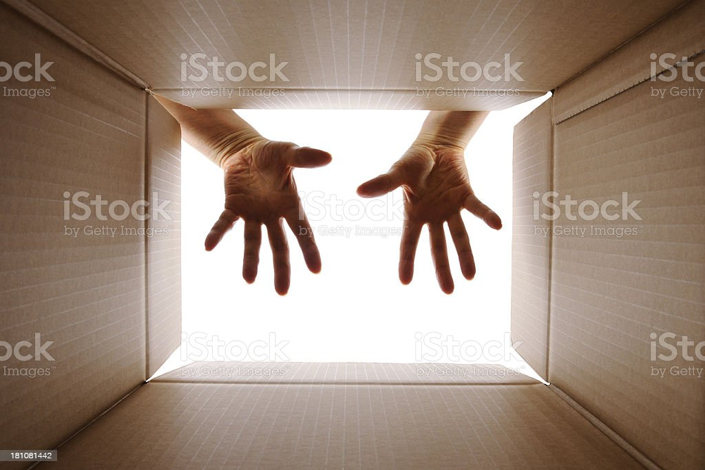 View from inside a cardboard box with surprised hands royalty-free stock photo