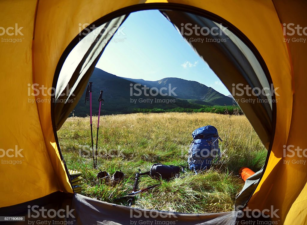 View from inside a tent on the girl and  mountains stock photo