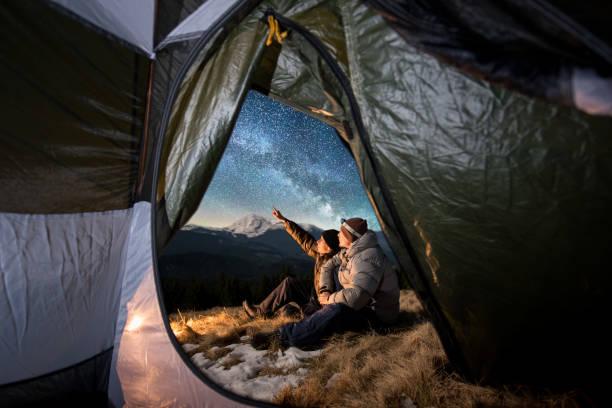 vue depuis l'intérieur d'une tente sur les deux touristes se reposer au camping dans les montagnes pendant la nuit. hommes assis près de feu de camp. un gars est pointant vers le ciel de belle nuit plein d'étoiles et de la voie lactée - astronomie photos et images de collection