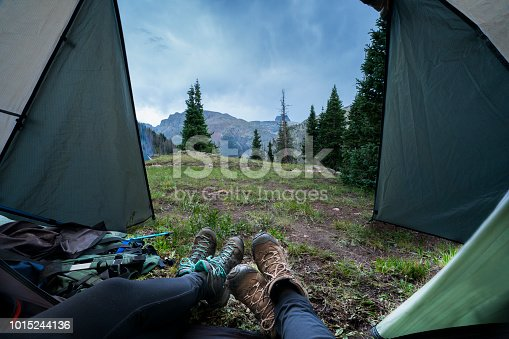 View from inside a tent with partial view of the boots and leggins of 2 people reclining after hiking in the mountains, Elk Creek campsite, San Juan Mountains, Weminuche Wilderness, Rocky Mountains, Silverton, Colorado, USA