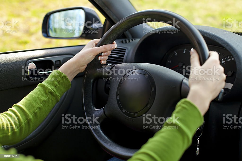 View from inside car at Women's Hands on steering wheel royalty-free stock photo