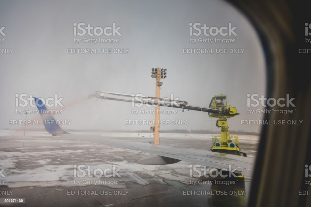 View from Inside the Plane of Spraying Anti-Freeze Liquid before Taking of. stock photo