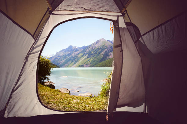 View from inside to outside Yellow tentA lake view. Camping in the woods. Mountain lake Kucherlinskoe from above, Altay, Russia stock photo