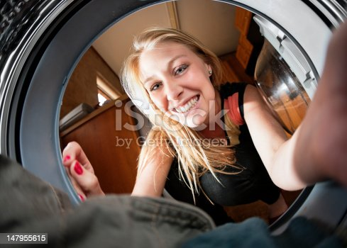 Seen from the inside of her washing machine and shot with fish-eye lens, a woman smiles. Shot with Canon EOS 1Ds Mark III.
