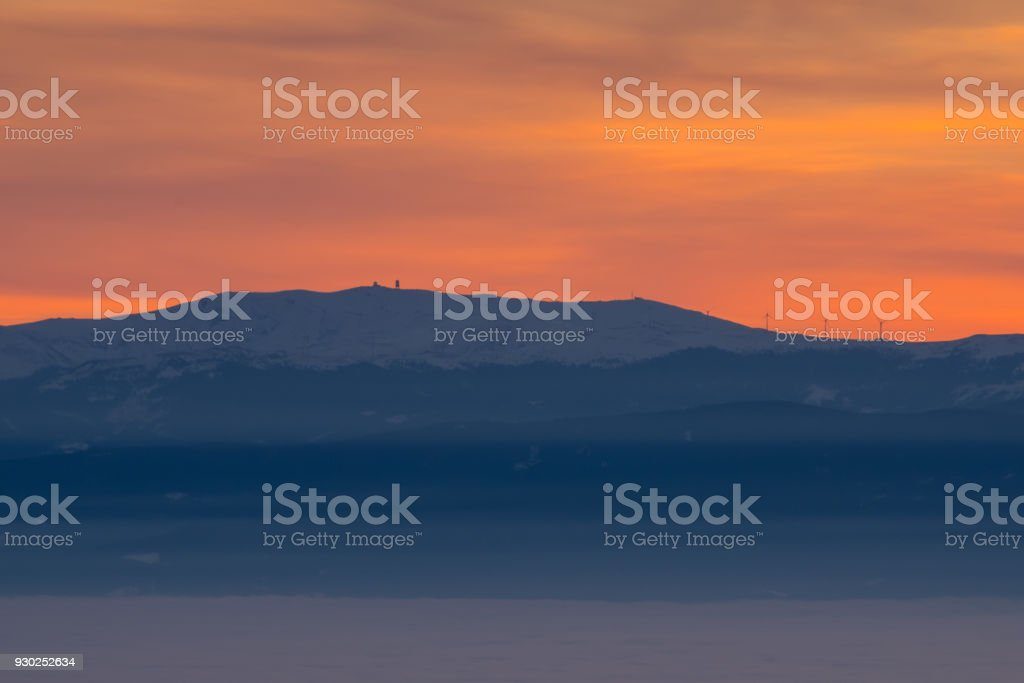 View from mountain Schoeckl over low stratus Koralpe with sunset stock photo