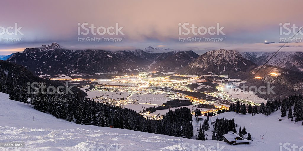 view from mountain to illuminated valley at winter stock photo