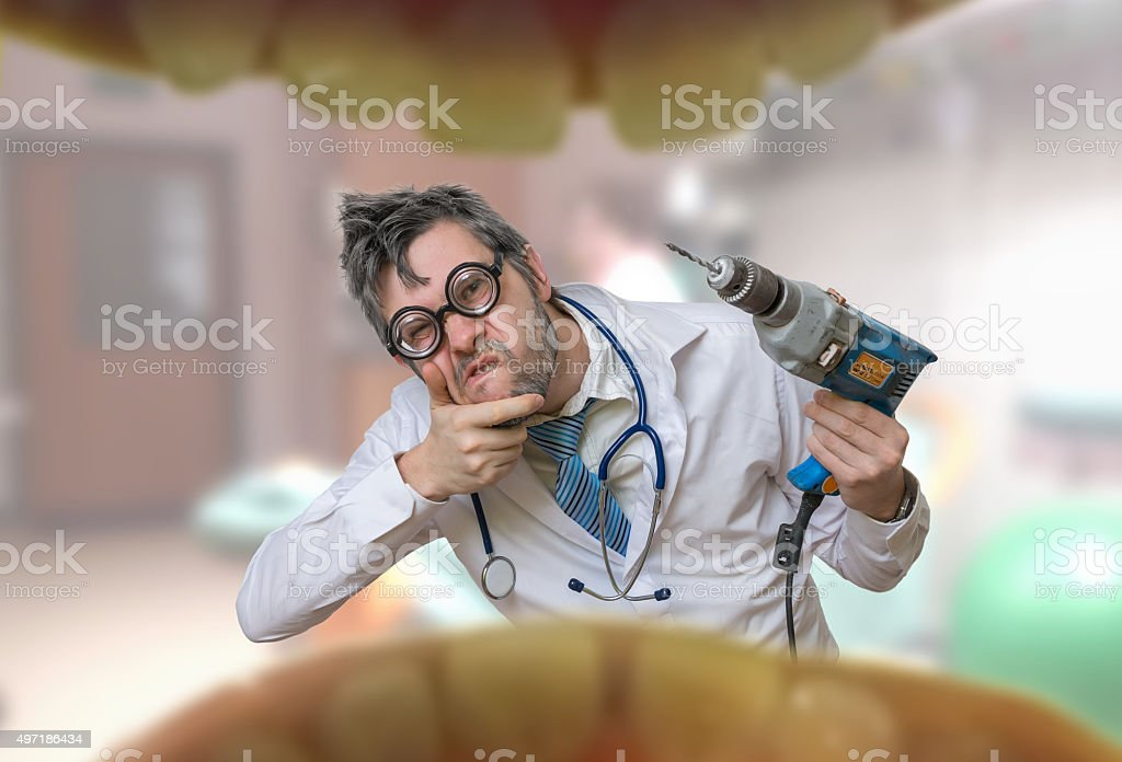 View from mouth on crazy unsure dentist doctor with drill stock photo