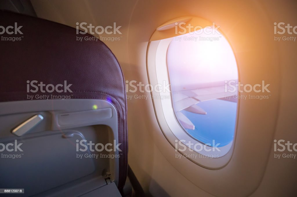 View from passenger's seat in airplane flying above clouds in dramatic sunset light. stock photo
