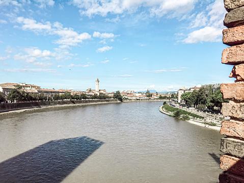 Riverside view of the Adige River from ponte di castelvecchio bridge built in 1350s with arches. Verona cityscape