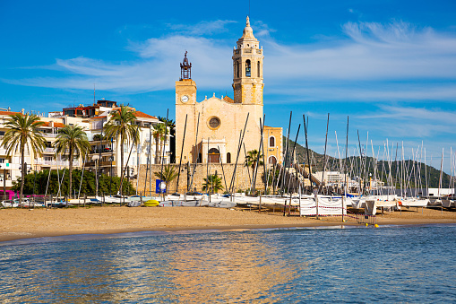 View from sea of Sitges beach and Church of St. Bartholomew and Santa Tecla on sunny fall day, Catalonia, Spain