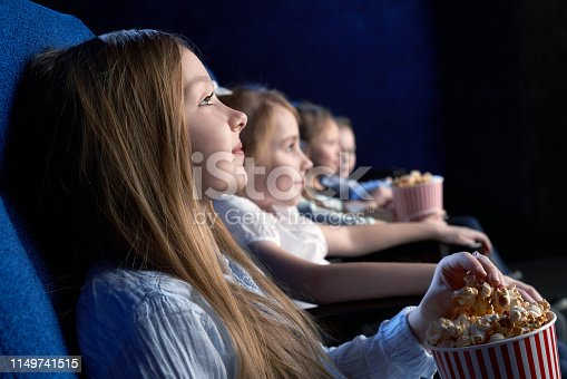 View from side of beautiful little girl sitting in cinema and watching interesting film. Young spectator resting with friends and eating popcorn. Concept of having fun and entertainment.