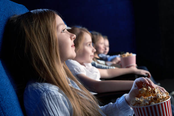 view from side of beautiful little girl sitting in cinema and watching interesting film. young spectator resting with friends and eating popcorn. concept of having fun and entertainment. - film industry stock pictures, royalty-free photos & images