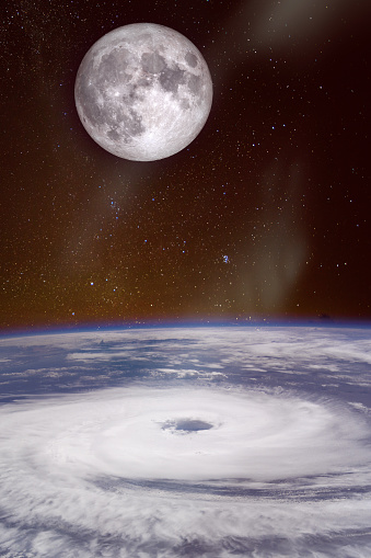 View from space of a giant hurricane over the ocean with full moon in background. The elements of this image furnished by NASA.