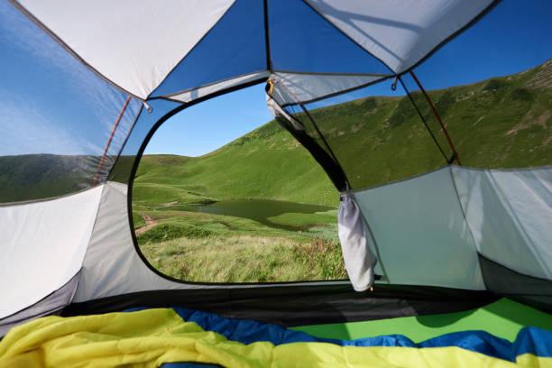 blick vom zelteingang am schönen see am morgen. camping in den bergen - zelt stehhöhe stock-fotos und bilder