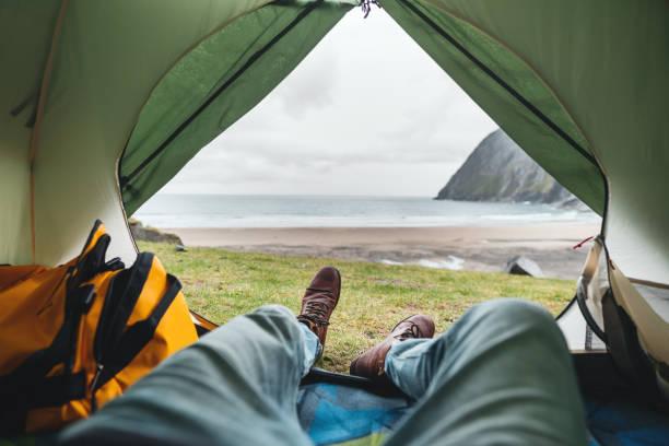 POV-Blick vom Zelt auf den Beinen mit Wanderschuhen vor Bergen und Meer. Allein Tourist ruht auf Camping am Meer – Foto