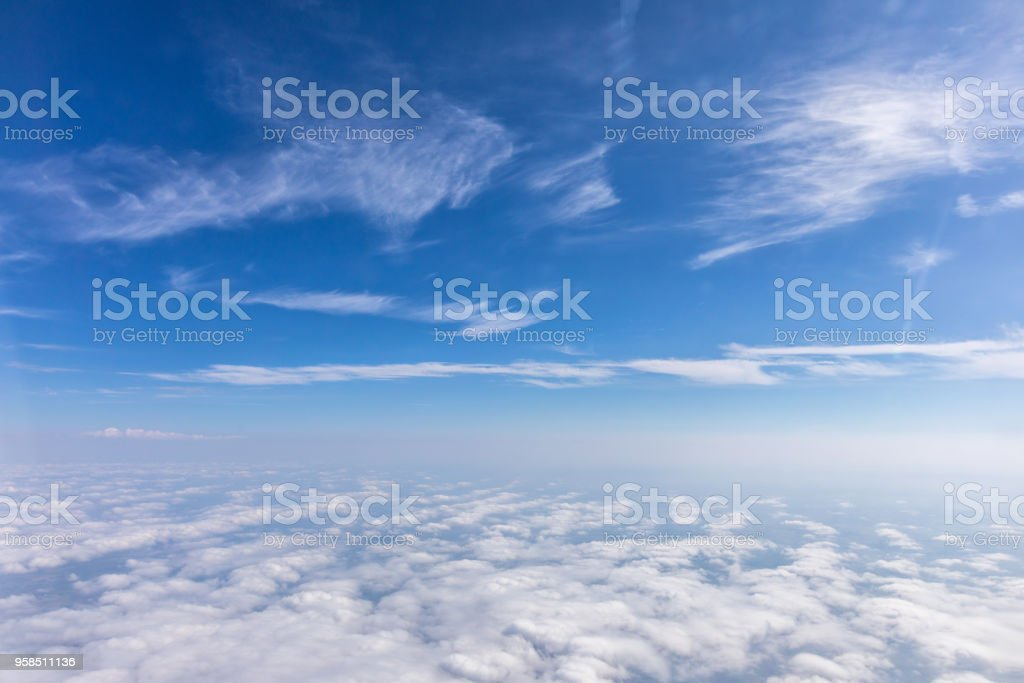 View from the airplane to the sky above the Alps mountains. Blue sky with clouds. Background. stock photo