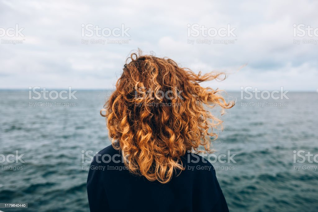 View from the back a woman with curly hair View from the back a woman with curly hair looks at the sea Adult Stock Photo